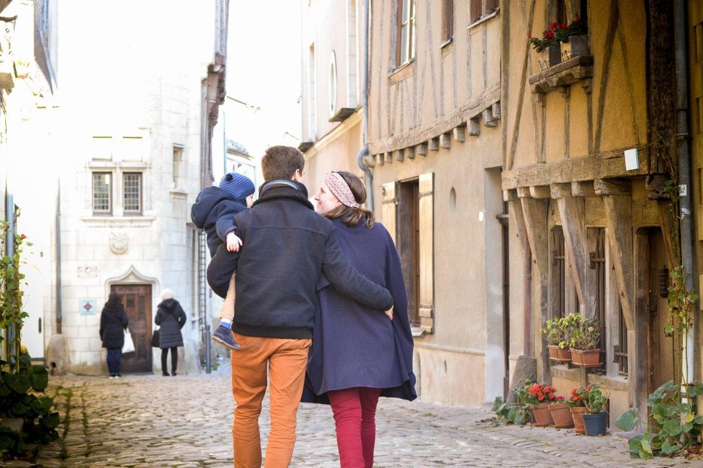 Jeune famille marchant dans une rue médiévale