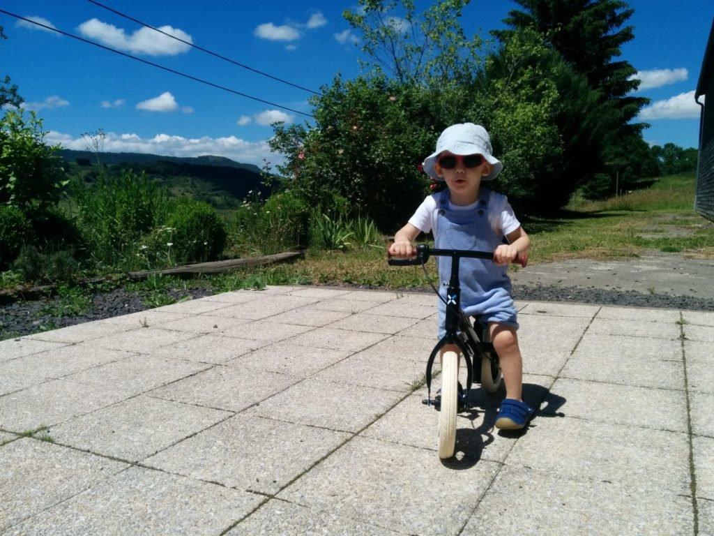 enfant sur un vélo avec un bob et des lunettes de soleil