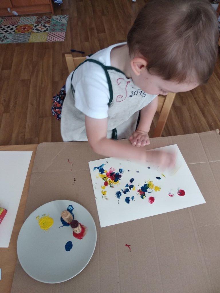 Enfant faisant de la peinture avec des bouchons de liège
