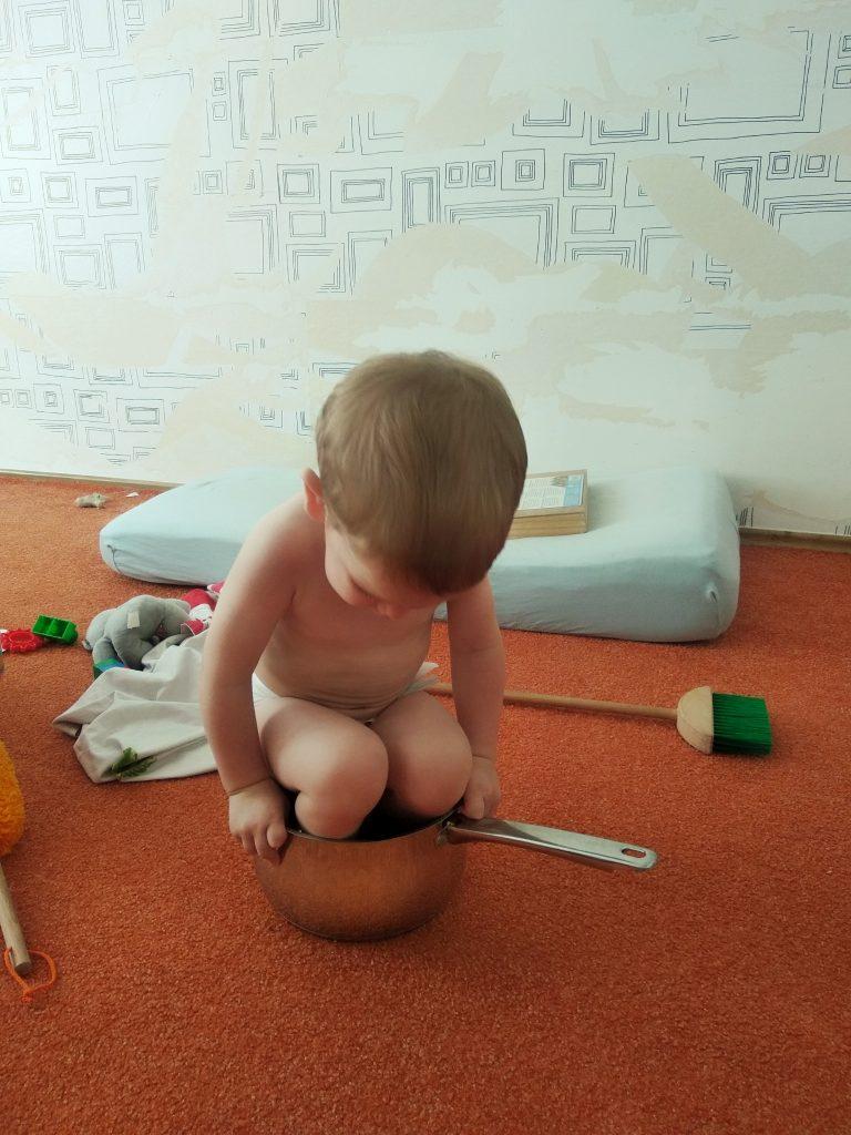 Enfant jouant dans une casserole